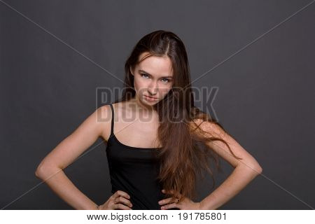 Angry woman with hands on hips looking at camera. Portrait of grumpy girl, dark background