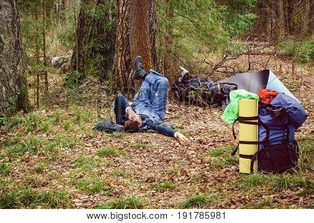 Man lying on grass near his backpack in a forest. A person rests after a long journey. Consolidated way of life and recreation in nature. Summer forest camp