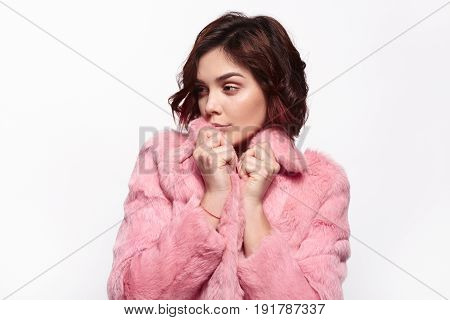 Attractive young girl looking away standing in the pink fur clothes. Horizontal studio shot.