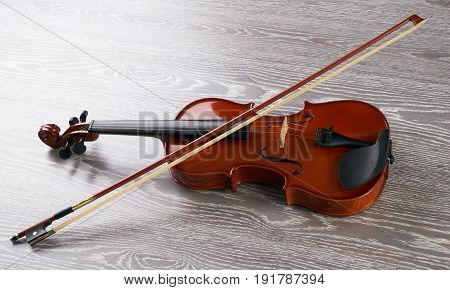 Violin with bow isolated on wooden background. Classical stringed musical instrument fiddle with fiddlestick.
