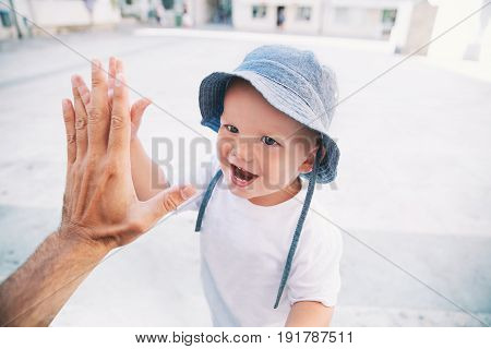 Cute boy son giving high five to father. Happy smiling portrait of child outside. Close-up of adorable kid enjoying summer vacation. Family Childhood Parenthood and People concept.