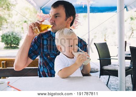 Father drinks beer child drinks juice in a beach bar. Dad and son are best friends! Family spend time together in a cafe restaurant in a summer day. Lifestyles Family Vacation concept.