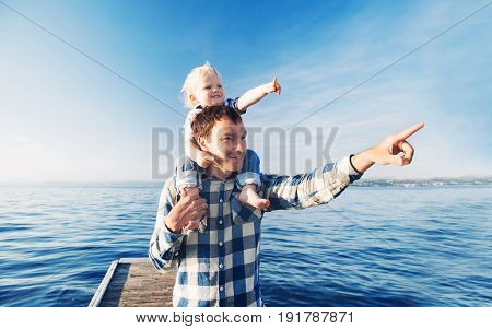 Father and son on sea and sky backgrounds. Little boy is sitting on father's shoulders and points forward. Parent and child together at summer. Family Lifestyle Holidays and Travel concept.