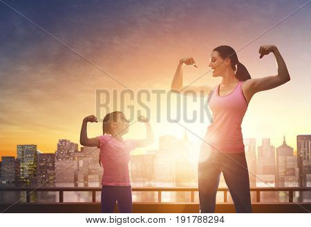Athletic young woman and her daughter are running on background of urban landscape. Healthy lifestyle. Family sport.