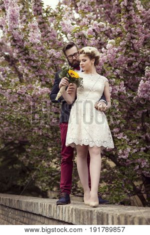 Newlywed couple standing in the street next to a cherry blossom tree hugging and holding a sunflower wedding bouquet