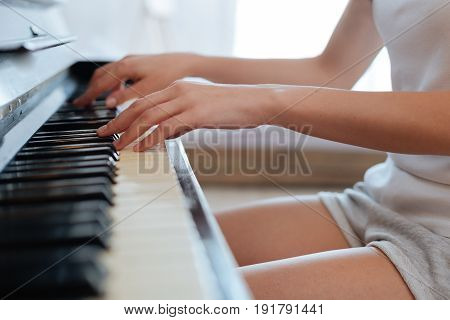 Playing and meditating. Female hands touching black and ivory keys while playing classical music on the piano at home.