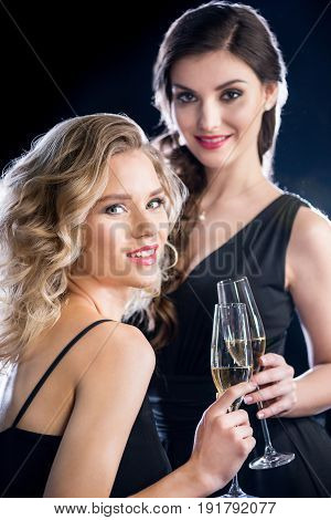 Gorgeous Smiling Young Women In Evening Gowns Holding Glasses Of Champagne And Smiling At Camera