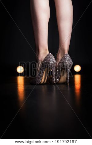partial view of woman standing in stylish sparkling high heels