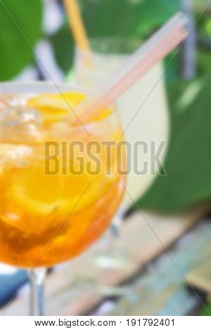 One glass of spritz aperol cocktail with orange slices; blurred background