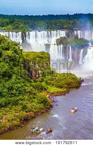 Small boats transport curious tourists to waterfalls.  Falls on the border of Argentina, Brazil and Paraguay. The concept of extreme and exotic tourism