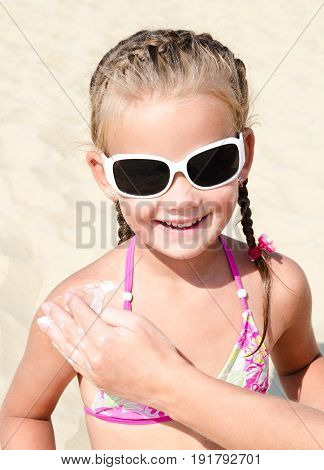 Mother anoints protective cream to body little girl child on the beach