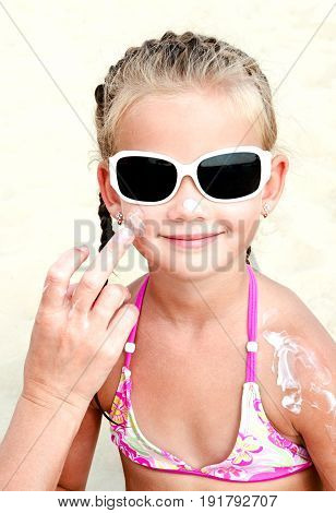 Mother anoints protective cream to face little girl child on the beach