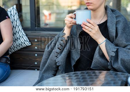 Close up young woman wrapped in grey plaid holding metal tea mug in outdoors restaurant