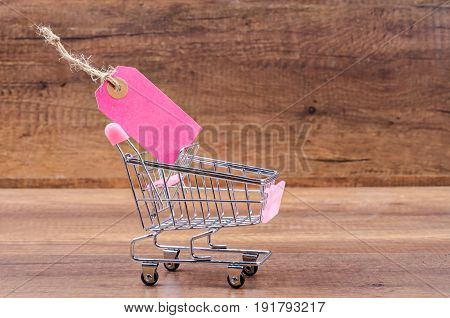 Blank pink paper price tag with shopping cart on wooden background
