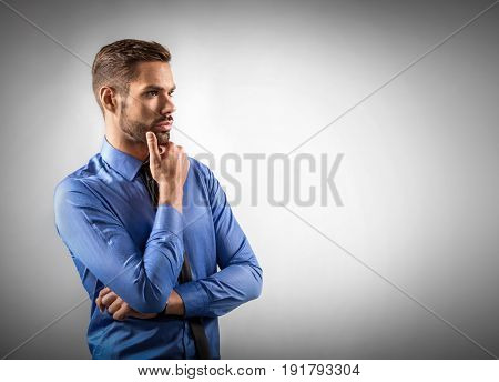 Young businessman thinking about new business ideas. Grey background copy-space.