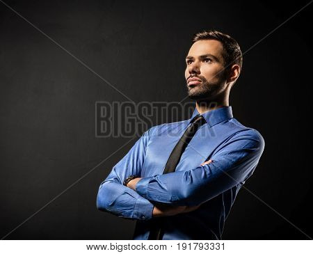 Handsome young businessman standing confident on black background. Smart boss, manager portrait with crossed arms