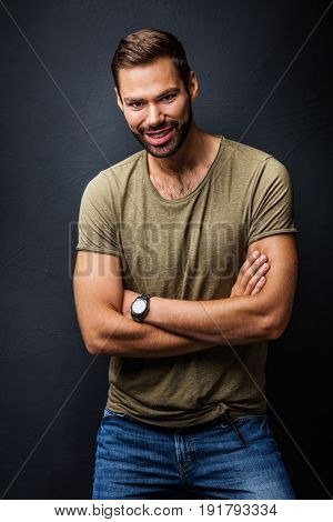 Handsome man smiling, standing confident with crossed arms. Black background