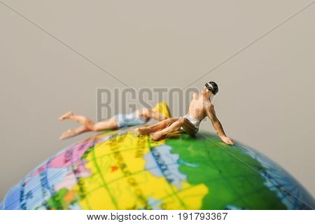 a miniature man and a miniature woman wearing both swimsuit on the top of the terrestrial globe