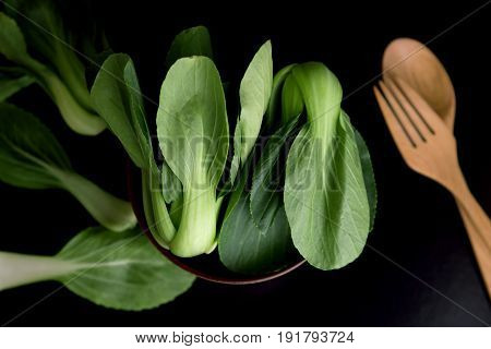 close up Fresh baby green bok choy in bowl with woodden spoon and fork on black background overhead or top view shot