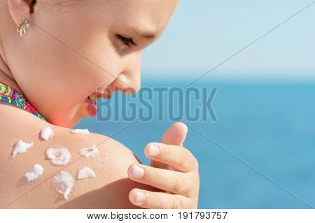 young girl applying sun protector cream on her shoulder on the beach close to tropical turquoise sea under blue sky at sunny day