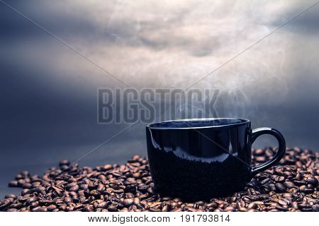 still life of the warm black cup of coffee on roasted coffee beans