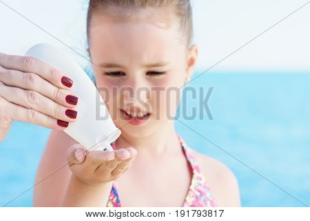 young girl taking sun protector cream from white tube for applyng it on her shoulder on the beach close to tropical turquoise sea under blue sky at sunny day.
