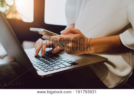 Soft focus of woman hand working with phone on desk in coffee shop. Vintage tone