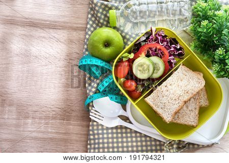 Healthy Lunch box with grain bread and fresh water drink bottle on wooden background Healthy eating clean food habits for diet concept top view and overhead shot