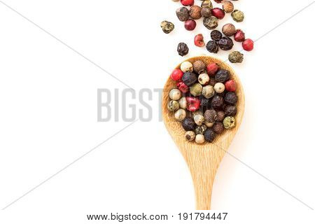 Close up mixed type of peppercorns in wooden spoon on white background top view or overhead shot