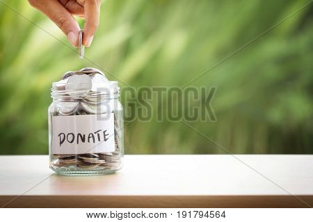 Hand putting Coins in glass jar for giving and donation concept