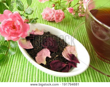 Cup of black tea with rose flowers