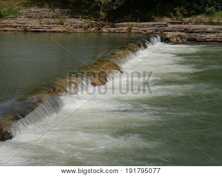 Cascading water in the river, wide view Water falls from a low layer of stones in the river