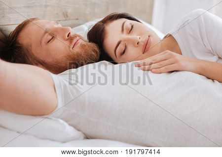 Seeing a common dream. Woman sleeping on her husband chest in bed while both relaxing at home after an intensive working day.