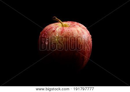 Red apple with drops of water in light and shadows