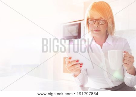 Beautiful mid adult businesswoman having coffee while using table PC at home