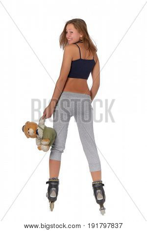 The beautiful girl with a toy bear in rollerskates on a white background.