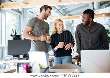 Image of happy young colleagues in office coworking using laptop computers and talking with each other. Looking aside.