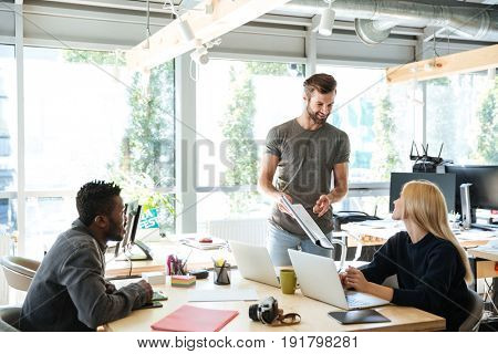 Image of smiling young colleagues sitting in office coworking using laptop computers and work with diagrama. Looking aside.