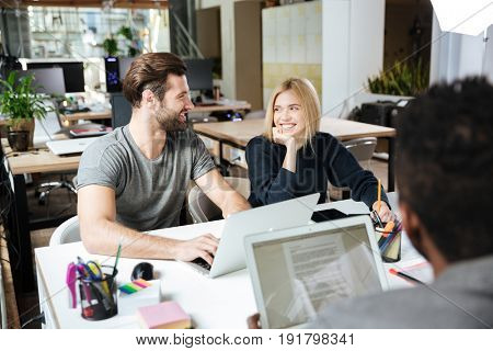 Image of happy young colleagues sitting in office coworking using laptop computers and tablet. Looking aside.