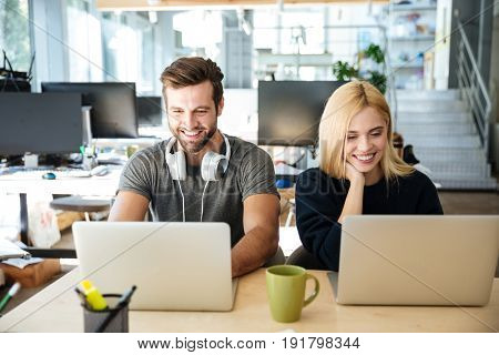 Photo of smiling young colleagues sitting in office coworking using laptop computers. Looking aside.