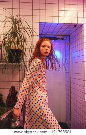 Fashion portrait of serious young redhead curly lady standing in cafe near latrine and plants. Looking at camera.