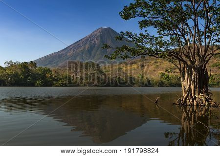 View of the Concepcion Volcano and its reflection on the water in the Ometepe Island Nicaragua; Concept for travel in Nicaragua and Central America