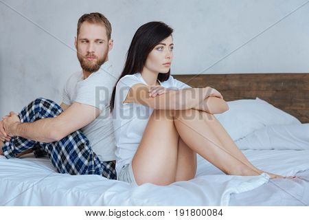 Back to back. Angry couple turning their back on each other after a conflict while sitting on a bed at home.