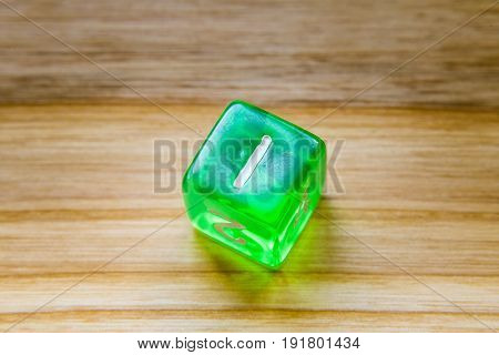 A Translucent Green Six Sided Playing Dice On A Wooden Background With Number One On A Top