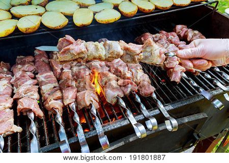 Grilling barbecue meat on wood coal. Man cooks appetizing hot shish kebab on metal skewers. Tasty meat pieces with crust. Grilling food. Cooking shashlik on barbecue grill. Closeup.