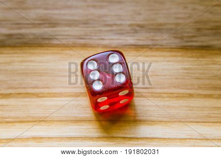 A Translucent Red Six Sided Playing Dice On A Wooden Background With Number Six On A Top