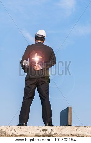 Back-view of businessman hand holding wind turbine.