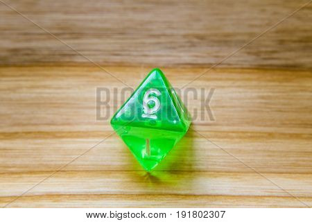 A Translucent Green Eight Sided Playing Dice On A Wooden Background With Number Six On A Top