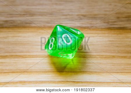 A Translucent Green Ten Sided Playing Dice On A Wooden Background With Number Zero On A Top