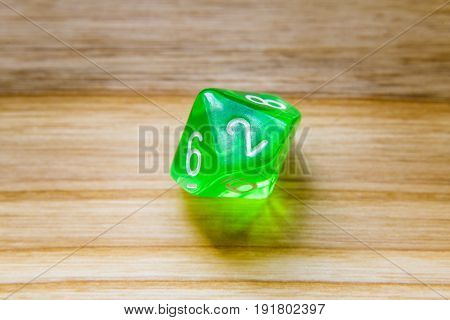 A Translucent Green Ten Sided Playing Dice On A Wooden Background With Number Two On A Top